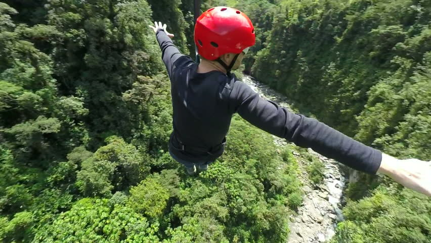 Adult men riding a zip line, cable mounted camera, model released ,camera spins around the model - HD stock footage clip