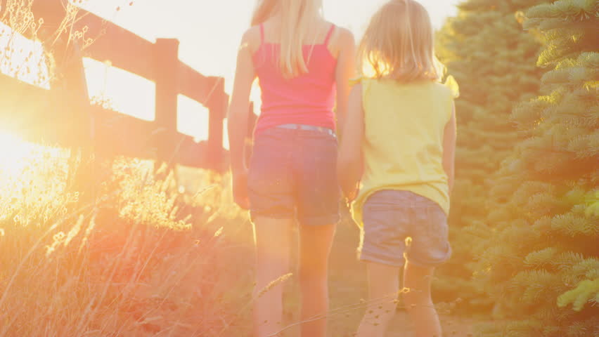 Young blonde sisters walking together outside - 4K stock video clip