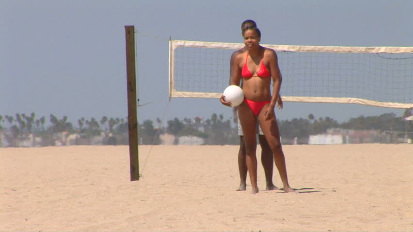 Young African American couple playing volleyball at the beach - HD stock footage clip