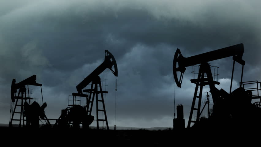 working oil pumps silhouette against the background of the dark storm clouds - HD stock video clip