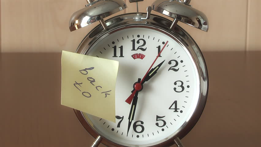 """An alarm clock and a yellow note with this text: """"Back to """""""