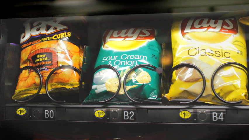 DALLAS, TX - FEB 23: Buying potato chip crisps from vending machine on February 23, 2015. Potato chips are a predominant part of the snack food market in Western countries.