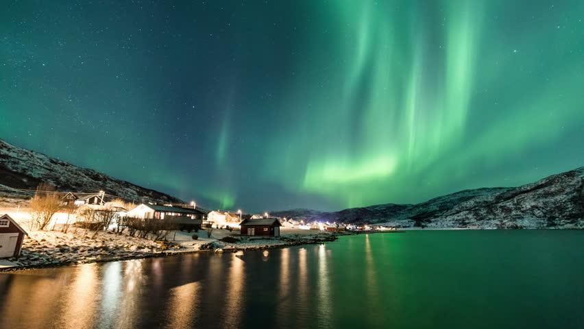 Northern Lights and city lights near Troms coast