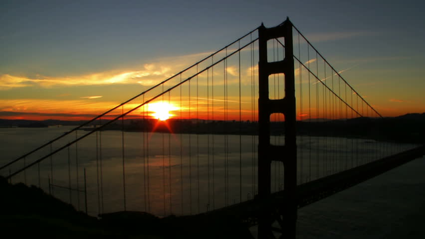 Time lapse footage of cargo ship crossing under Golden Gate Bridge at sunrise in San Francisco, California