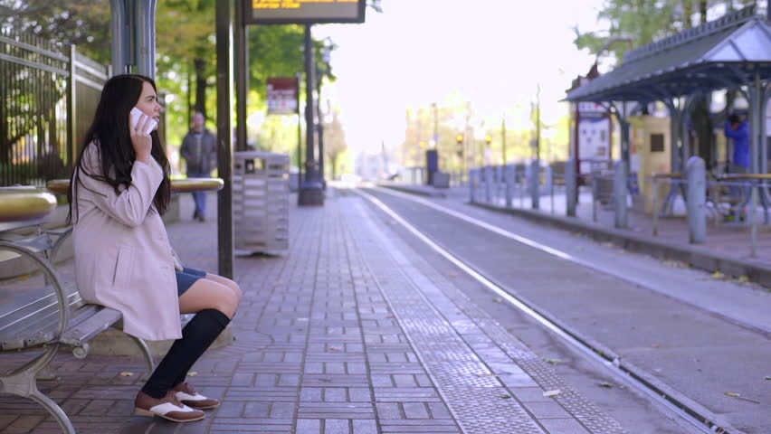 Mixed Race Young Woman Sits On Bench At Train Stop And Talks On The Phone