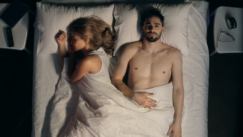 Direct from above view of couple in bed, woman sleeping, man tossing sleeplessly