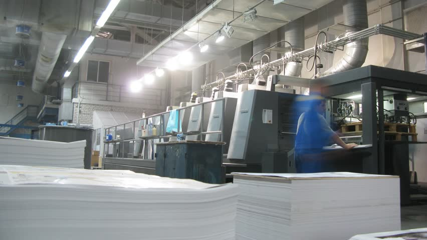 RUSSIA, MOSCOW - NOV 29, 2014 (Time Lapse): Workers work in printing machines, in the foreground a pile of sheets of paper