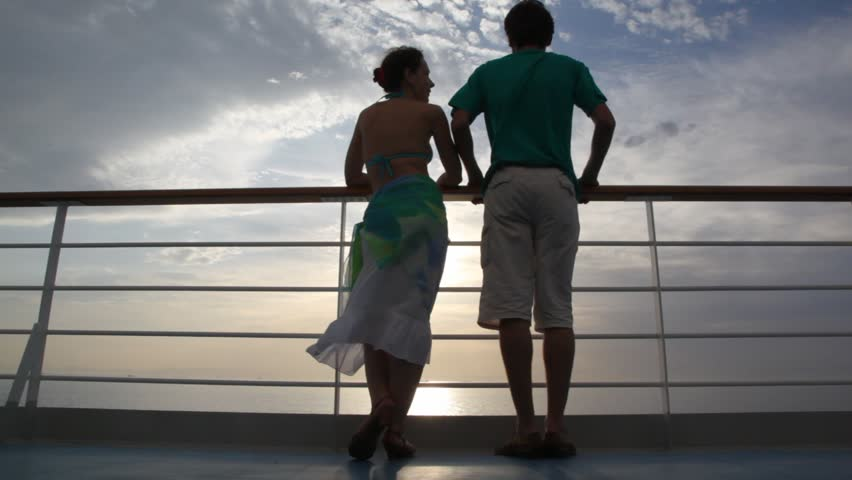 young couple stands on deck of cruise ship and talks against sunset sky #910378