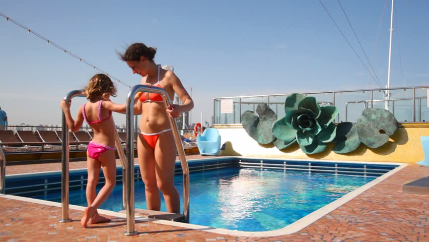 young mother with little daughter in bikini near swimming pool on cruise ship - HD stock video clip