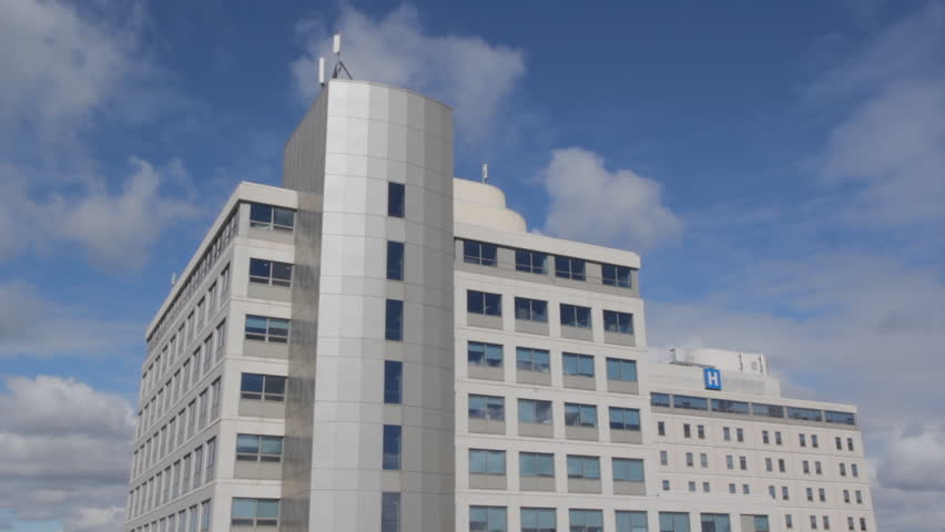 Hospital with blue sky and time-lapse clouds moving overhead.