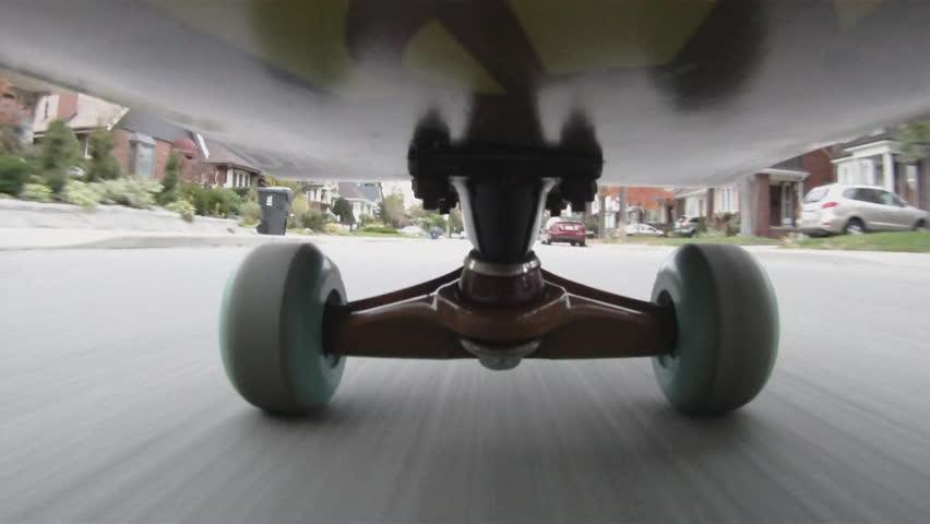 Riding a skateboard down an urban street. Toronto, Ontario, Canada.