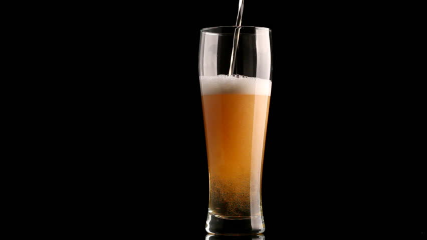 Beer poured in glass on black background