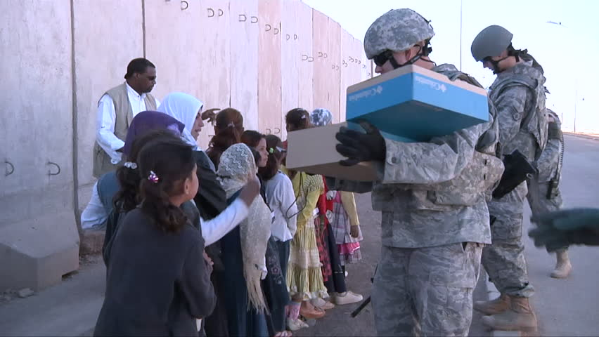 CIRCA 2010s - Kids take handouts from U.S. soldiers in Iraq.