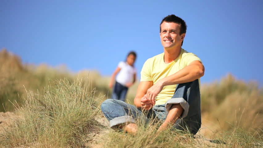 Young caucasian father with his mixed race daughter having fun together in the sand dunes by the coast
