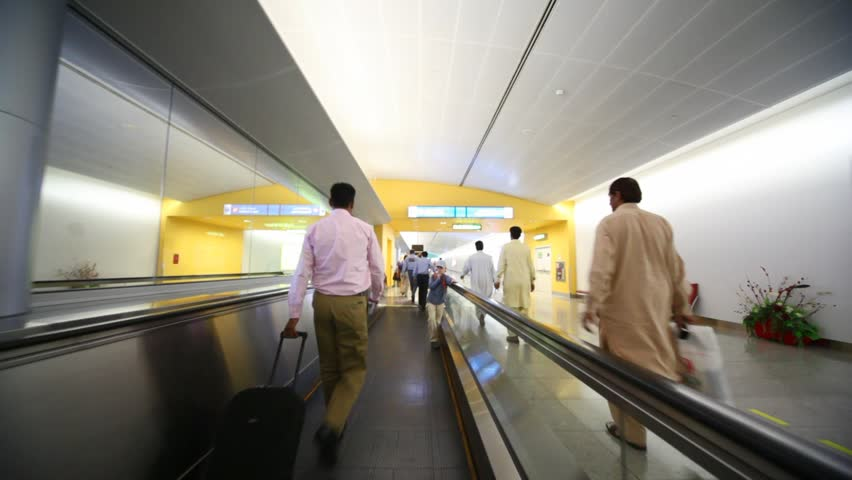 DUBAI - APRIL 13: People on travelator or moving walkway in Dubai International Airport on April 13 2010. The airport was the 15th busiest airport in the world by passenger traffic handling 40.9 million passengers in 2009.