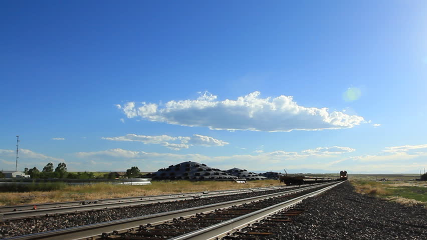 Locomotive under cloudy skies in rural Colorado. Extreme dramatic perspective.