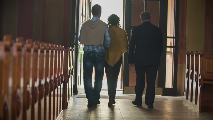 SENTJUR, SLOVENIA - OCTOBER 2014: Priest escort the lovely couple to the door. Slow motion footage of a couple being escorted out side by the priest from the catholic church in the sunny day. - HD stock footage clip