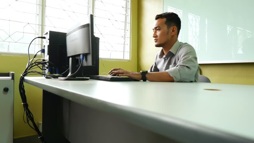 Young and ambitious male employee work with his computer and feeling happy, dolly shot
