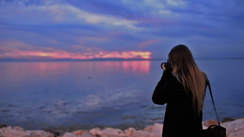 Woman taking landscape photos with a dslr camera.