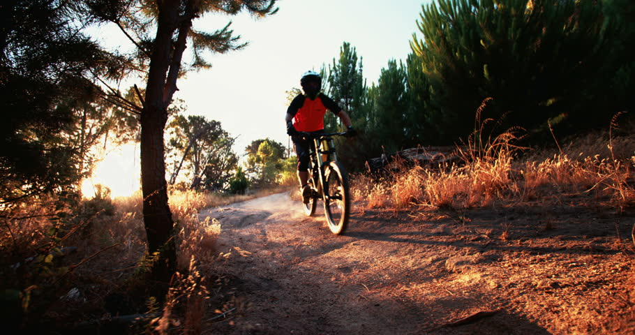 Adventurous mountain biker riding a forest track on a trail ride at sunset, slow motion