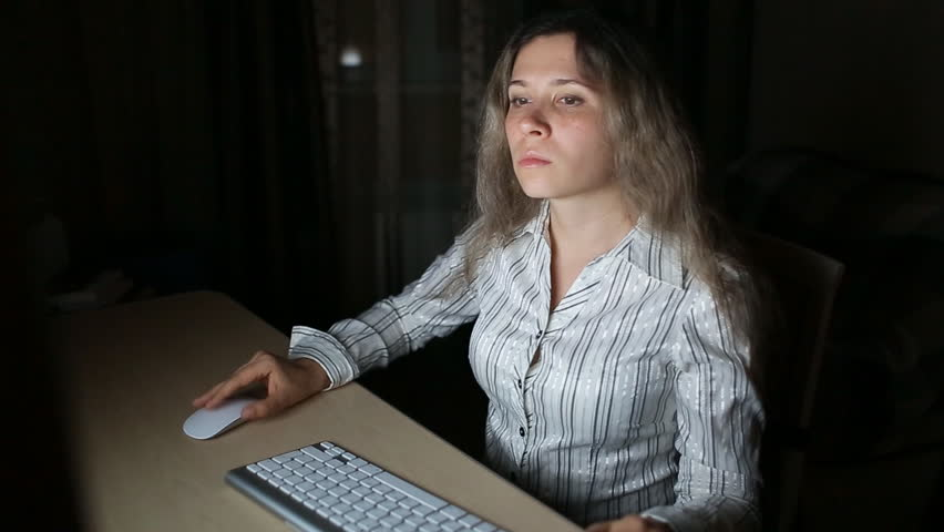 Lady working late. Surfing the internet