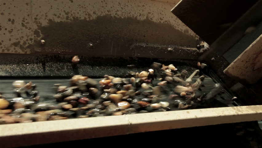 Sand and stones falling and then going on conveyor belt. Separation of sand in the construction industry. Separating sand and small stones. Wet sand falls on conveyor. Pile of sand. Open pit. Close up