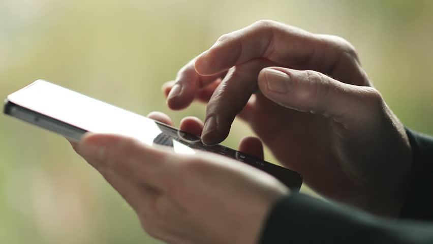 Business woman writes a message on Smartphone