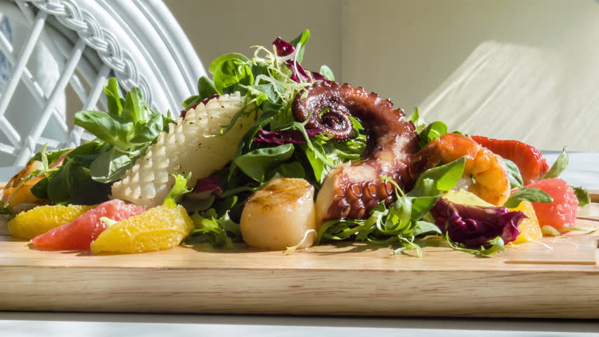 It is so tasty. Selective focus on nourishing appetizing salad or savory consisted of shrimps lettuce and cheese preparing by chef cook standing on wooden support near glass of water and white vintage
