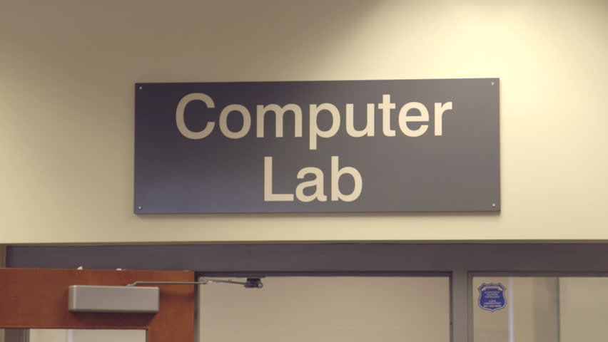 """Tilt shot from a """"computer lab"""" sign down to people working on computers"""