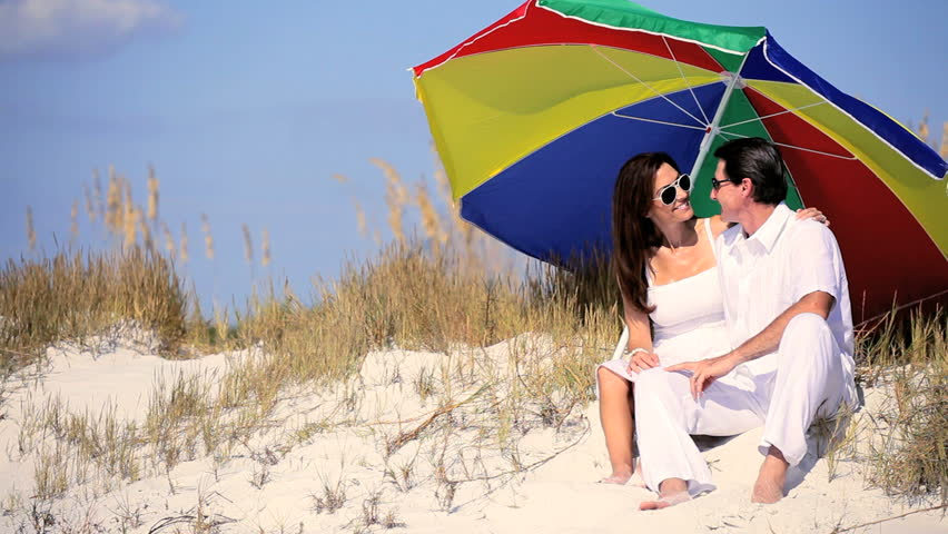 Attractive healthy young couple sitting under a sun parasol on the beach - HD stock footage clip