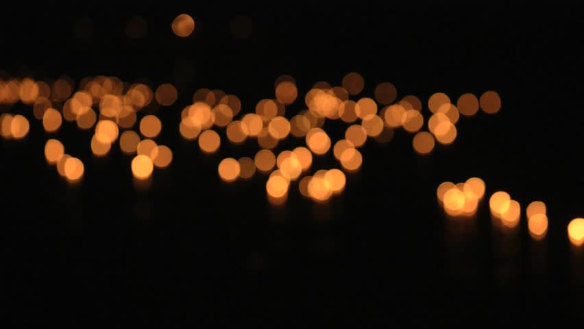 Burning candles float on water during Loi Khrathong celebration in Sukhothai, Thailand. Deep out of focus.