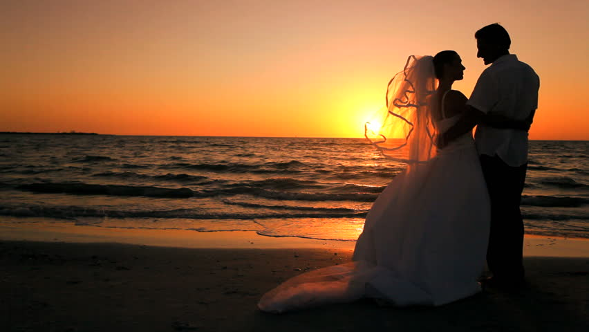 attractive couple exchanging a kiss at their sunset
