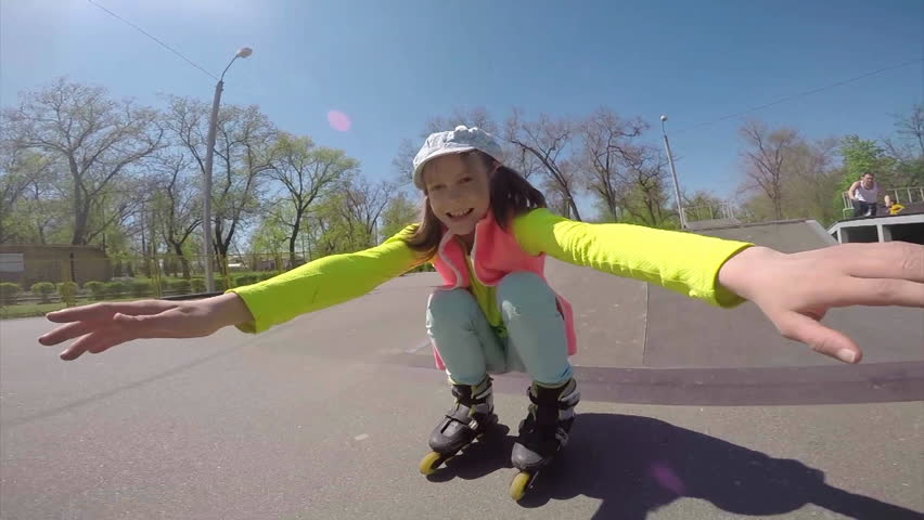 Outdoor portrait of a sportive child inline skates blading in the park. Slow motion. Childhood, sports, active lifestyle concept. - HD stock video clip