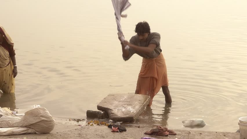 Varanasi, india, man washing clothes in sacred ganges river, february 2015. The Ganga has an extraordinary religious importance for Hindus.