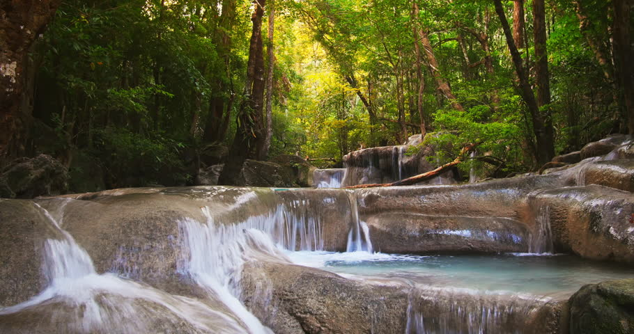 Beautiful water stream with cascades and small waterfalls flows through wild tropical rain forest full of green plants and trees with green leaves. Tracking slider video shot  - 4K stock footage clip