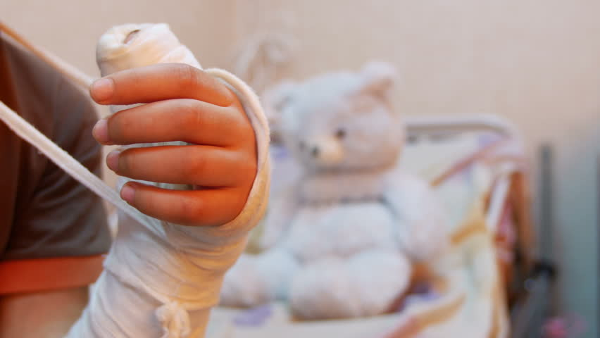 Child hand in plaster recovery near a teddy bear in a hospital room
