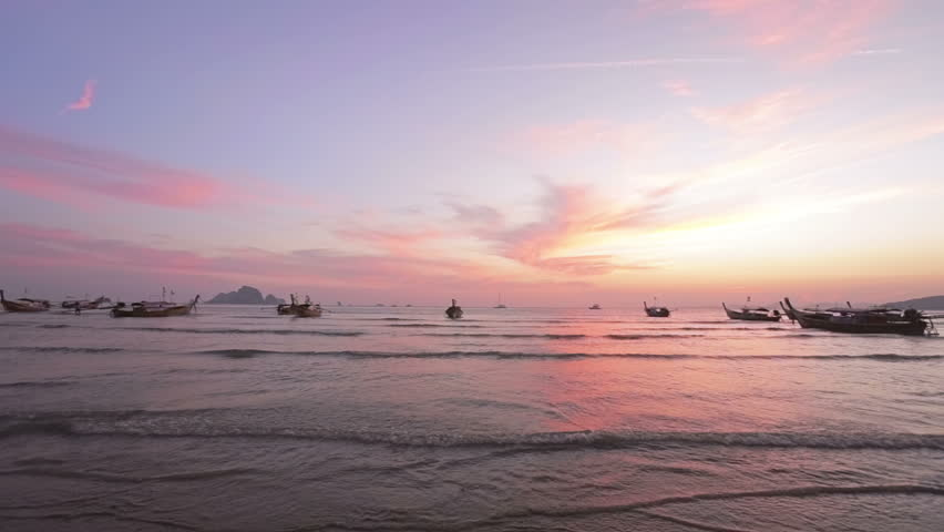 Beautiful sunset at the beach with boats.  Boats in the sea at sunset time. Krabi, Thailand